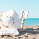 shutterstock_437089297_portrait-of-a-young-brunette-relaxing-on-the-beach-reading-a-book.jpg