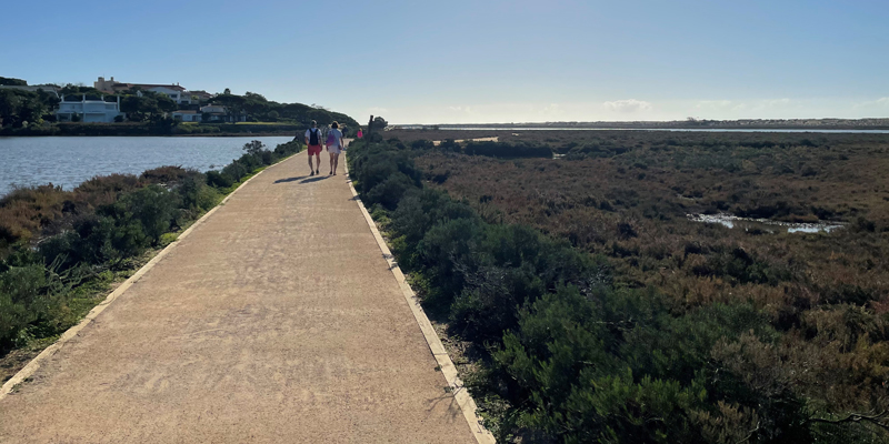 Couple walking on a pedestrian road by the Ria Formosa in the Algarve