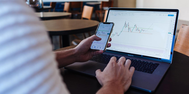 Man looking at laptop and mobile with forex app open