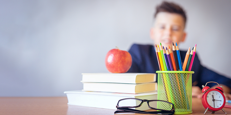 Blurred image of a boy sitting at a desk with books, pencils and a pair of glasses to symbolise the importance of doing an eye check-up in children