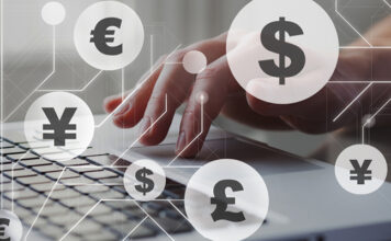 Person typing on laptop keyboard with Euros and Pounds symbols over the image to simbolize the currency exchange business of Privalgo